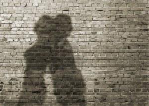13710948-sombra-del-hombre-y-la-mujer-en-la-pared-de-ladrillo-sucio